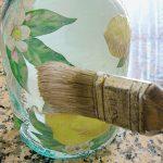 Pennello che stende colla decoupage su bottiglia di vetro